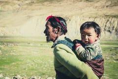 Un agricoltore tibetano con il suo bambino fotografie stock
