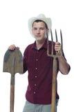 Un agricoltore in un cappello con una pala e una forca a disposizione Fotografia Stock Libera da Diritti