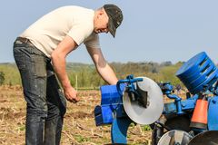 Un agriculteur ajustant la charrue au match de labourage Photo stock