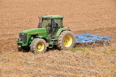 Un agriculteur avec un tracteur labourant la terre avant 068 de ensemencement Photo stock