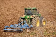 Un agriculteur avec un tracteur labourant la terre avant 074 de ensemencement Image libre de droits