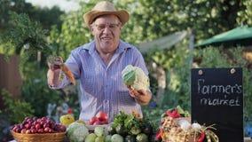 Un agriculteur plus âgé vend des légumes sur le marché de ferme banque de vidéos