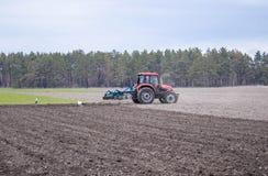 Un agriculteur sur un tracteur prépare la terre avec un cultivateur Encemencement sur les champs agricoles image libre de droits