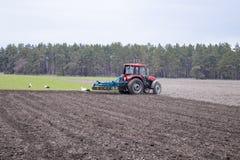 Un agriculteur sur un tracteur pr?pare la terre avec un cultivateur Encemencement sur les champs agricoles photos stock