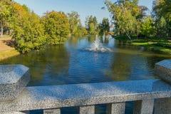 Un agua de rociadura de la pequeña fuente a lo largo de la superficie del ` s del lago en un parque con los árboles que cuelgan e Fotos de archivo