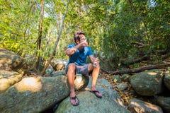Un agua potable del hombre de la botella pl?stica encendido en la naturaleza pura del bosque relaja concepto foto de archivo libre de regalías