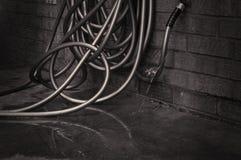 Un agua que se escapa de la manguera de jardín en el pavimento Imagen de archivo