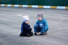 Un ahd del muchacho una muchacha que juega en el asfalto Foto de archivo libre de regalías