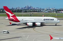 Un Airbus A380 da Qantas con l'orizzonte di Sydney Immagine Stock