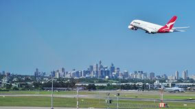 Un Airbus A380 da Qantas con l'orizzonte di Sydney Fotografia Stock