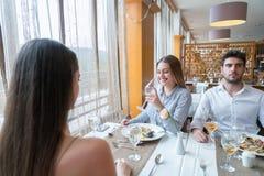Un ajouter à un ami féminin ayant la conversation dans un restauran Photos stock
