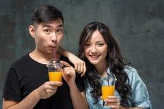 Un ajouter assez asiatique de jeunes à des verres de jus d'orange Photographie stock libre de droits