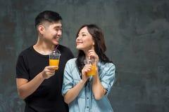 Un ajouter assez asiatique de jeunes à des verres de jus d'orange Photo stock