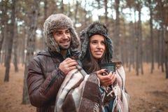 Un ajouter dans des vêtements chauds et à une couverture se tient dans une forêt et examine la distance Photo libre de droits