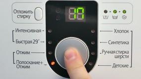 Un ajuste masculino de la mano y una lavadora electrónica de gama alta de torneado encendido almacen de metraje de vídeo