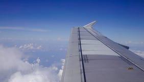 Un ala del aeroplano a través de la ventana foto de archivo libre de regalías