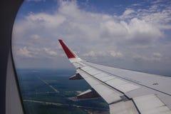 Un ala del aeroplano a través de la ventana fotos de archivo