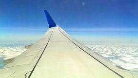 Un'ala dell'aeroplano da una fodera del getto alta sopra il paesaggio Immagine Stock
