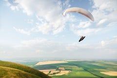 Un ala flexible blanco-anaranjada vuela sobre el terreno montañoso imagen de archivo libre de regalías