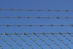 Un alambre y una cerca de púas de metal contra el cielo azul 1 imagen de archivo libre de regalías