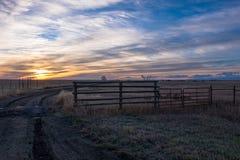Un'alba dorata che aumenta sopra un Rancher& x27; campo di s con i cieli variopinti Fotografie Stock Libere da Diritti