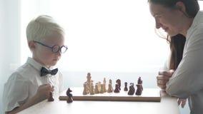 Un albino joven que juega con su madre en ajedrez almacen de metraje de vídeo