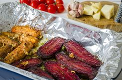 Un alimento sano Le barbabietole e le carote aromatizzate risiedono in una forma di cottura accanto alla grattugia dei pomodori,  immagini stock