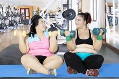 Un allenamento grasso di due donne con le teste di legno Fotografie Stock