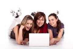 Un allievo dei tre giovani con il computer portatile Fotografia Stock Libera da Diritti