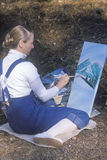Un allievo di arte che vernicia uno scenico, Immagine Stock