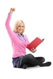 Un allievo femminile felice che legge un libro Immagini Stock