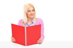 Un allievo femminile felice che legge un libro Fotografia Stock Libera da Diritti