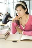Un allievo femminile sta studiando Immagini Stock