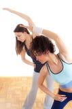 Un allungamento grazioso delle due ragazze di forma fisica Fotografia Stock