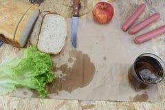 Un almuerzo del ` s del constructor, una tabla de trabajo de madera en el emplazamiento de la obra con la comida y herramientas d Foto de archivo