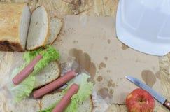 Un almuerzo del ` s del constructor, una tabla de trabajo de madera en el emplazamiento de la obra con la comida y herramientas d Imagen de archivo