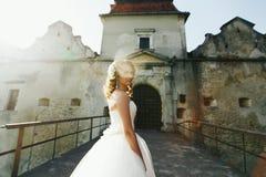 Un alone di luce solare intorno alla sposa che sta nella parte anteriore di vecchio Fotografie Stock