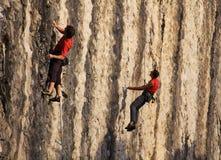 Un alpinismo di pratica di due scalatori sulla parete di pietra verticale Immagini Stock Libere da Diritti