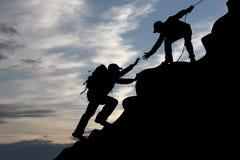 Un alpinista dei due turisti del viaggiatore su alba Immagini Stock Libere da Diritti