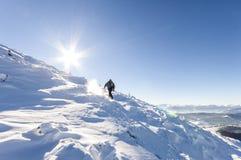 Un alpinista maschio che cammina in salita su un ghiacciaio Reac dell'alpinista Fotografie Stock