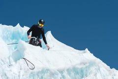 Un alpinista professionale in un casco ed in una passamontagna sull'assicurazione dentella l'ascia di ghiaccio nel ghiacciaio Il  Immagini Stock Libere da Diritti