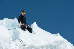 Un alpinista professionale in un casco ed in una passamontagna sull'assicurazione dentella l'ascia di ghiaccio nel ghiacciaio Il  Fotografia Stock