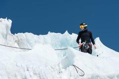 Un alpinista professionale in un casco ed in una passamontagna sull'assicurazione dentella l'ascia di ghiaccio nel ghiacciaio Il  Fotografie Stock