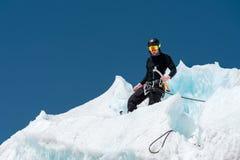 Un alpinista professionale in un casco ed in una passamontagna sull'assicurazione dentella l'ascia di ghiaccio nel ghiacciaio Il  Fotografia Stock Libera da Diritti