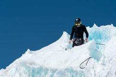 Un alpinista professionale in un casco ed in una passamontagna sull'assicurazione dentella l'ascia di ghiaccio nel ghiacciaio Il  Immagine Stock