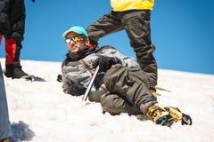Un alpinista in un riposo di menzogne dell'attrezzatura professionale e del punto soleggiato su un pendio nevoso circondato dai s Fotografia Stock Libera da Diritti