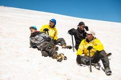 Un alpinista in un riposo di menzogne dell'attrezzatura professionale e del punto soleggiato su un pendio nevoso circondato dai s Fotografia Stock