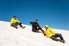 Un alpinista in un riposo di menzogne dell'attrezzatura professionale e del punto soleggiato su un pendio nevoso circondato dai s Immagini Stock