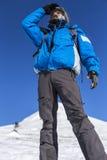 Un alpinista sulla cima di una montagna nevosa Immagini Stock
