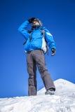 Un alpinista sulla cima di una montagna nevosa Immagine Stock Libera da Diritti